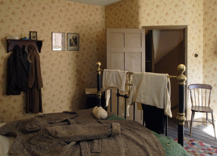 A view of the 1930s house bedroom at the Birmingham Back to Backs showing the bed and bedstead with a coat spread over it for additional warmth