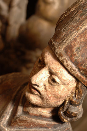 Close view of the head of a carved wooden figure of a bishop, part of the collection in Nadir at Snowshill manor