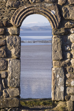 A view through one of the carved stone arched windows of St Patricks Chapel, Heysham Head, looking towards Morecambe Bay, Lancashire