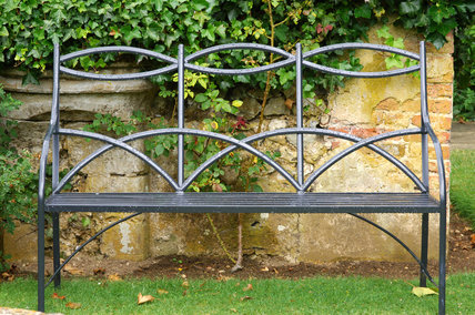 A graceful metal garden bench at Mottisfont Abbey