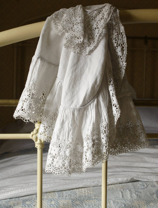A lace-trimmed shift hung over the iron bedstead of the bed in the 1870s house second floor bedroom at Birmingham Back to Backs