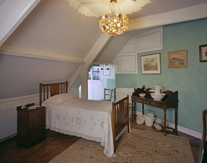 Second floor Bedroom at A la Ronde, with sloping eaves, simple furniture and a  lampshade made from shells