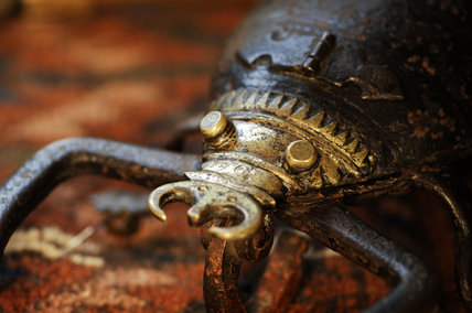 Close view of an iron and brass lockable box in the form of a scorpion, used to store herbal remedies