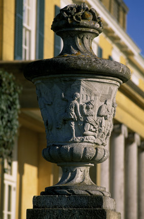 Close-up of a stone urn carved with classical scenes, against the colonnaded south terrace of Polesden Lacey