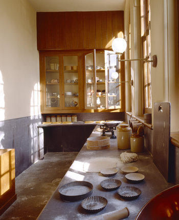 Pastry room showing slate benches with pastry and tins, sieve and weighing machine