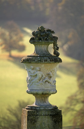 Closeup of a carved stone urn in classical style, on the south facing lawn of Polesden Lacey