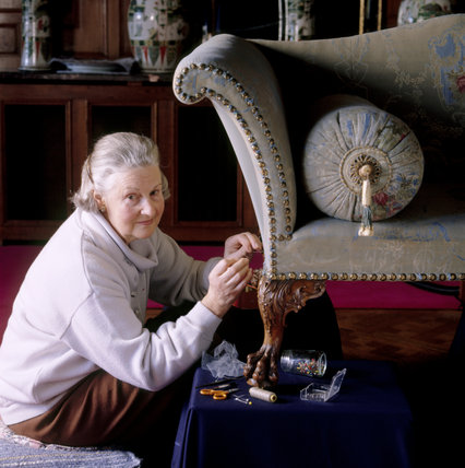 A National Trust volunteer carefully restores a blue and green patterned sofa at Nostell