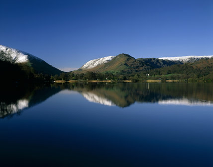 Looking down the length of the lake in Grasmere, to the magnificent snow capped hills in the distance, with the scene reflected in the shimmering water