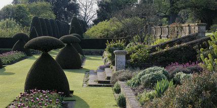 View of the Sunken Garden at Hinton Ampner showing the topiary, steps and flowering borders in springtime