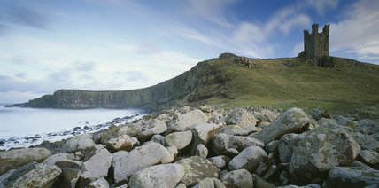 View of Dunstanburgh Castle from the north west showing the rocky coastline and cliff face