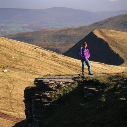 Walker on the summit of Corn Du looking east to the western ridge and summit of Cribyn