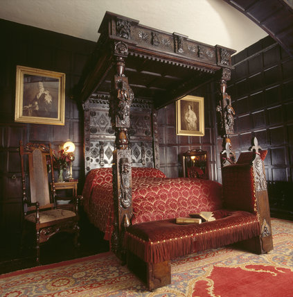 The interior of the Oak Bedroom revealing the elaborate and ornately carved bed