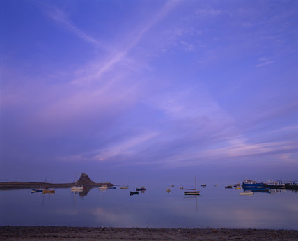 Distant view of Lindisfarne Castle at dusk, with boats moored at anchor in the foreground