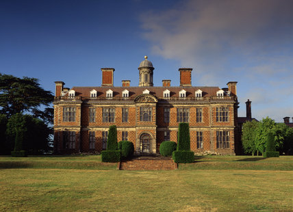 A view of the south front of Sudbury Hall against the blue sky, taken from the lawn with the brick steps in the foreground