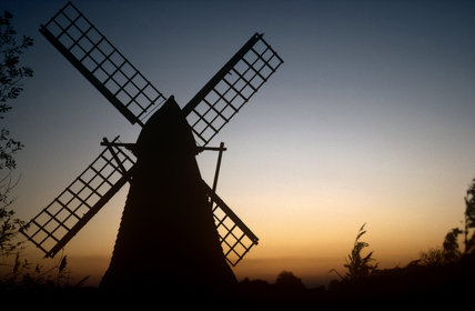View showing silhouette of windwill set against orange sky