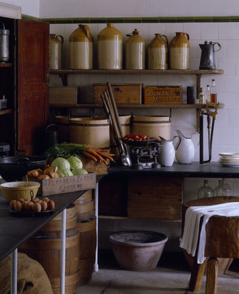 A corner of the Larder with various storage containers, jugs and a set of scales