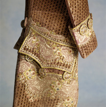View of a 1770s court coat made of velvet embroidered with silk & chenille thread with a design of flowers, leaves & buds