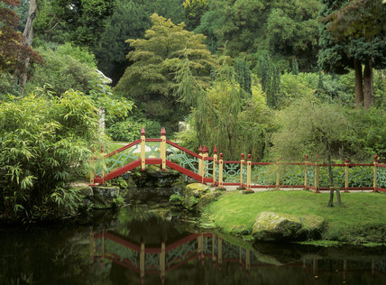 View from the Chinese temple in Biddulph Grange Garden across the lake to the wooden footbridge in China, a Victorian setting created to display exotic plants brought from the Far East