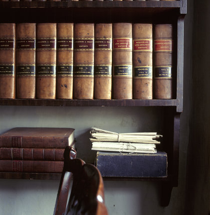 Close view of bookshelves in W.M. Heelis' offices, now Beat- rix Potter Gallery, showing leather bound volumes and bundles of papers on tables underneath.