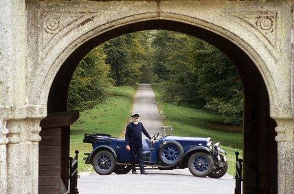 The Chauffeur standing in front of a 1929 Humber 16/50 Tourer used to transport visitors in the grounds of Lanhydrock