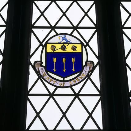 A close up of a stained glass window with the Watt emblem