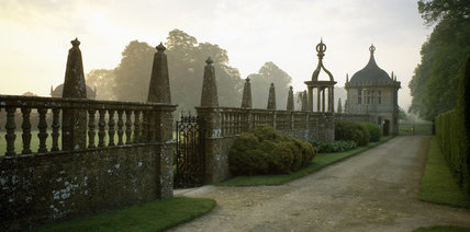 The East front terrace of Montacute House bounded by a balustrade and garden pavilions on a misty morning