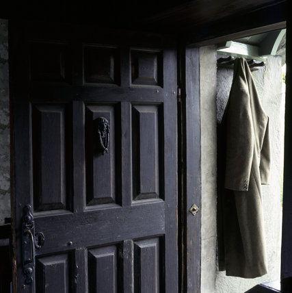 (FL) Close view of the substantial oak front door at Hill Top, which is unusual in having nine raised and fielded panels; it is hung on long iron strap-hinges with a cast iron door knocker