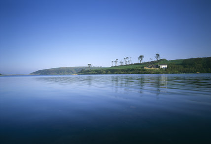 Lower Pentire Farm, National Trust holiday cottage, perches at the water's edge at Looe Pool in Cornwall