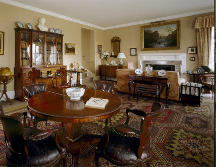 The Drawing Room at Trerice showing a late eighteenth century mahogany bookcase with glazed Gothick doors, tables, chairs and a collection of various ceramics