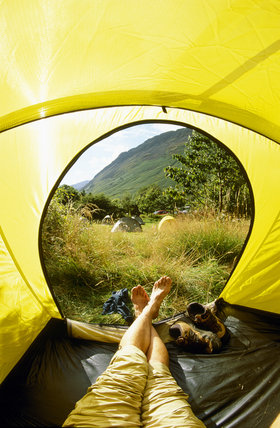 N.T.campsite at Wasdale Head, Cumbria, looking out from a tent over other tents in a field and towards big hills beyond.