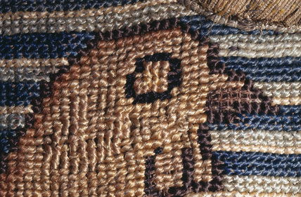 The head of a bird against a blue & white striped background as part of a motif from the Marian Needlework at Oxburgh Hall