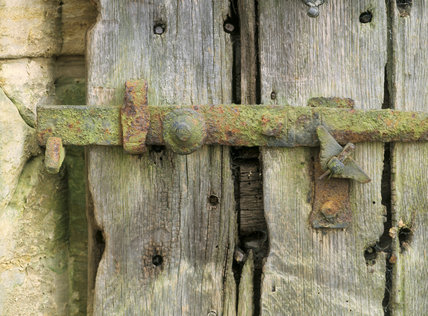 Close view of a weathered and rusted latch on an old wooden door at Nymans Garden