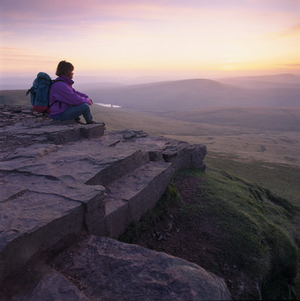 View of a lone rambler enjoying the spectacular twilight on Corn Du, Brecon Beacons, looking south west