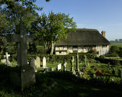 View across the graveyard to Alfriston Clergy House on a spring day, with stone cross and tulips in shadow in the foreground