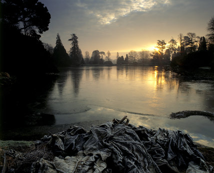 A view of a lake at Sheffield Park Garden, taken at dawn in January with the trees in silhouette