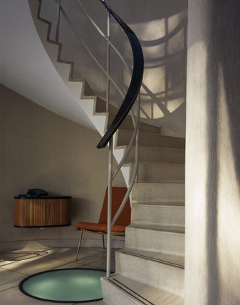 The striking central spiral staircase in The Homewood was designed by Patrick Gwynne and is made of concrete with a terrazzo finish illuminated by a sunken uplighter at the base