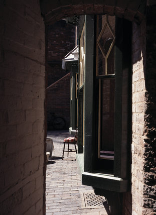 View through Arch into Courtyard of 1930's Back to Backs showing windows and brickwork with chair and laundry tubs visible
