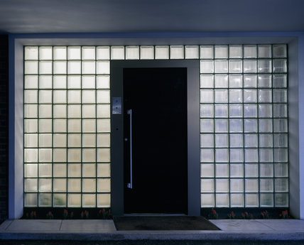 The front door of The Homewood designed by Patrick Gwynne is beneath the dramatic car-port canopy and surrounded by square glass blocks which encase the door in light