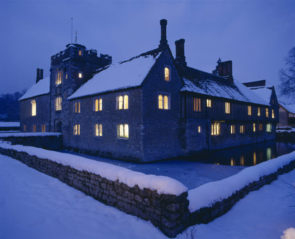 Ightham Mote under snow, at twilight with brightly lit windows, a view across the moat taken in February 1991
