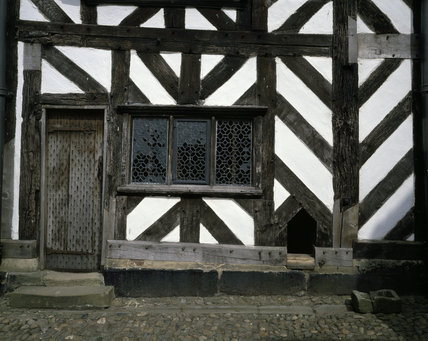 View of the half-timbered wall in the courtyard showing door and leaded window