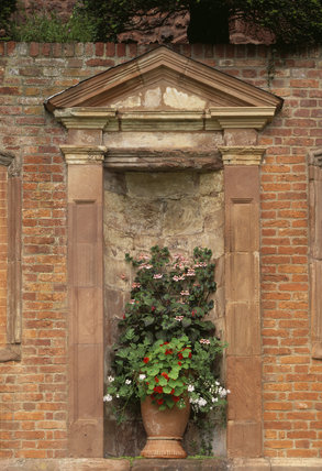 View of a container planted with nasturtiums and other plants standing in one of the niches in the centre of the Top Terrace at Powis Castle
