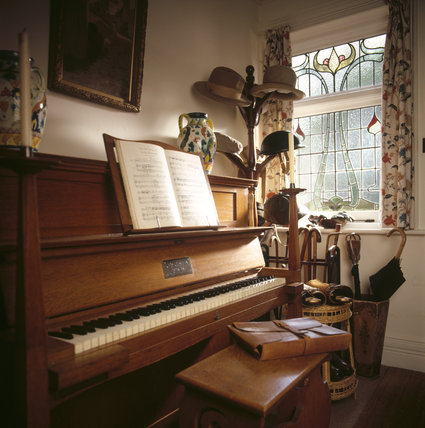 Room view of the Entrance Hall showing a Bechstein piano by the window with a satchel on the stool, hats, walking sticks, gaiter and music book open at Shaw's Corner
