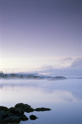Misty view at dawn of boats on Windermere, seen from Cockshott Point, with very still water and a mauve sky