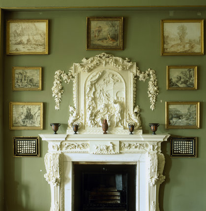 A partial view of the top of a marble chimneypiece and plaster overmantel in the Library brought from Wavendon in 1913