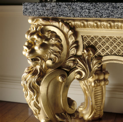A close-up detail of a carved and gilded table leg in the shape of a lion's head in the Dining Room at Ickworth
