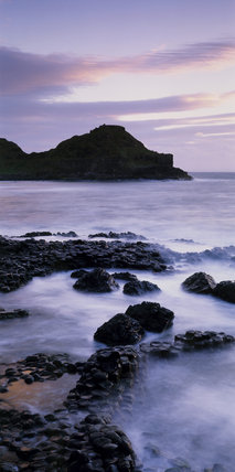 Close view of a section of the Giant's Causeway in silhouette seen across rocks and a misty mauve coloured sea in a clear light and calm conditions