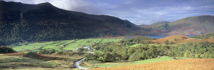 Overall view of Buttermere Valley showing the lake at the end of the valley with a river and a farm, bracken in the foreground and two hilly ranges behind