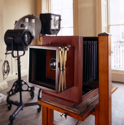 The Studio at 59 Rodney Street, Liverpool, the E. Chambre Hardman Studio, House and Photographic Collection - showing a large format camera and studio lights in the background.