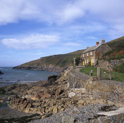 Quay Cottage a stone building sitting on the edge of a rocky foreshore with spectacular views out to sea at Portquin Bay
