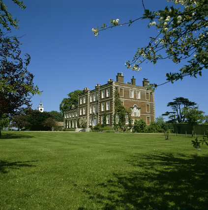 Gunby Hall, view across the lawn to the entrance of the red brick house built in 1700, with blossom in the foreground